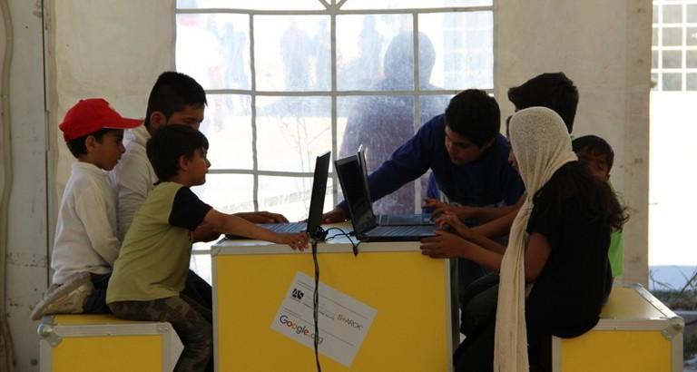Photo d'enfants utilisant les ordinateurs de l'Ideas Box dans le camp de réfugiés d'Eleonas à Athènes