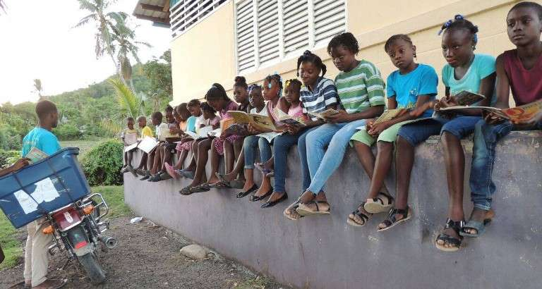 Photo d'enfants qui lisent a cote d'une bibliomoto à Haiti