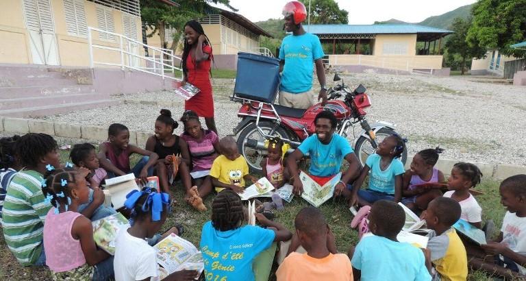 Photo d'enfants qui lisent pres d'une bibliomoto à Haiti
