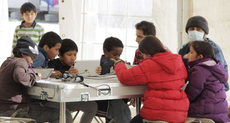 Picture of children using the tablets of the Ideas Box at the Eleonas refugee camp in Athens