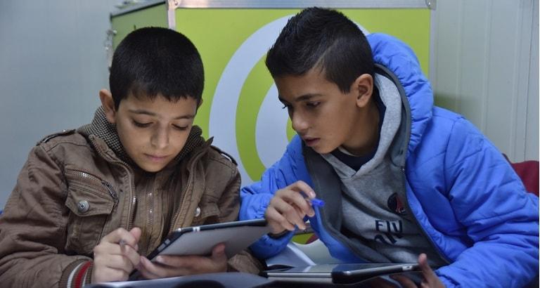 Utilisation des tablettes de l'Ideas Box à Hashmi El Shemali, Amman, Jordanie © Agnès Montanari / Bibliothèques Sans Frontières