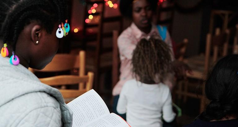 Photo d'une jeune fille qui lit dans un hôtel du Samu Social