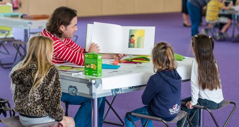 Photo de petites filles lisant un livre avec un animateur à Calais