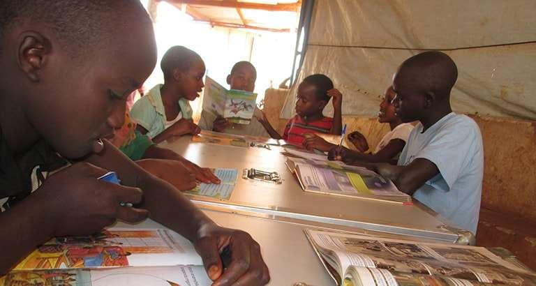 Photo d'enfants réfugiés lisant des livres de l'Ideas Box au Burundi