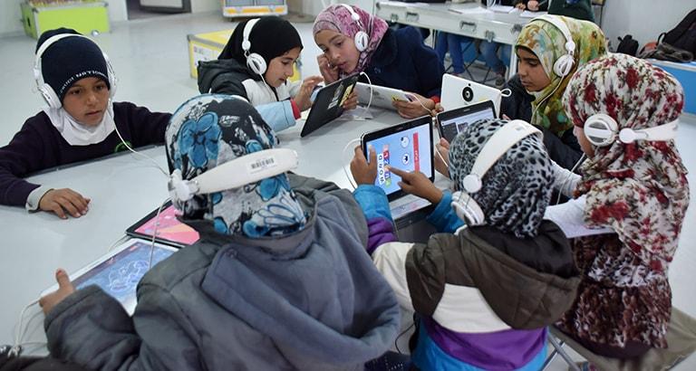 Photo d'enfants réfugiés utilisant les tablettes de l'Ideas Box en Jordanie