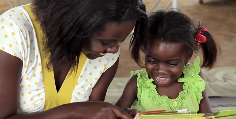 Photo d'une mère et sa fille lisant un livre dans un camp de réfugiés au Burundi