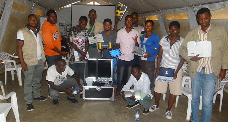 Photo des jeunes réfugiés congolais et de l'équipe d'EYE posant avec le KoomBook