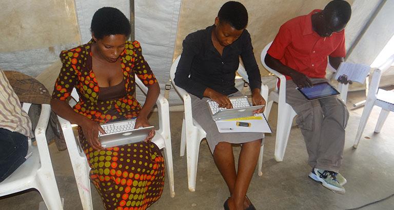 Photo de femmes réfugiées au Rwanda utilisant les tablettes du kit KoomBook