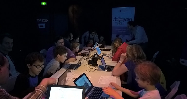 Photo d'enfants apprenant à coder sur des ordinateurs.