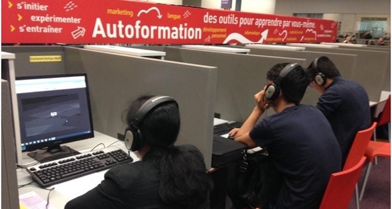 Photo de demandeurs d'asile devant des ordinateurs