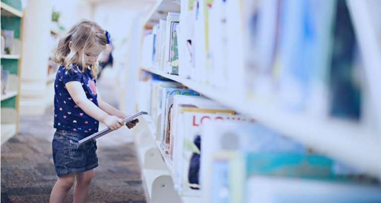 Photo d'une petite fille regardant un livre dans une bibliothèque