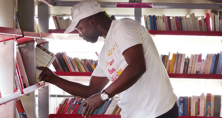 Photo d'un animateur rangeant un livre dans le bibliobus à Yaoundé
