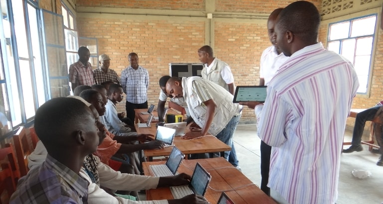 Photo des mineurs du centre de Rumonge assis devant les tablettes du kit KoomBook