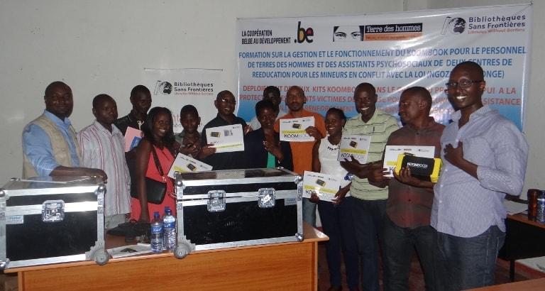 Photo du personnel de Terre des Hommes et des assistants psycho-sociaux posant avec le kit KoomBook au Burundi