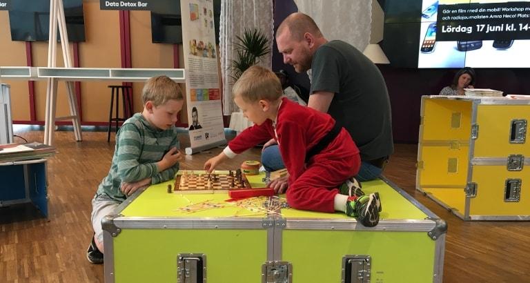 Photo d'un père et son fils jouant aux échecs sur l'Ideas Box à Stockholm