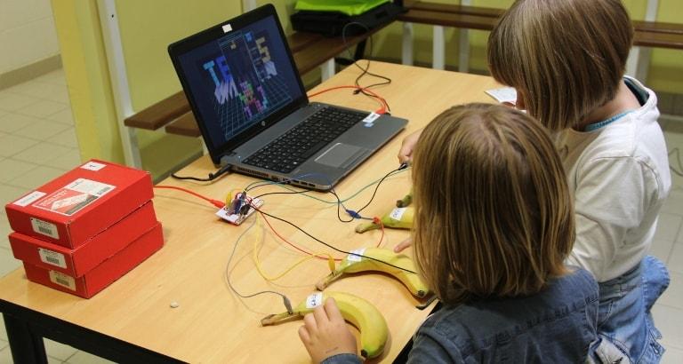 Photo de deux jeunes filles qui jouent au Tétris pendant l'atelier de Makey-Makey