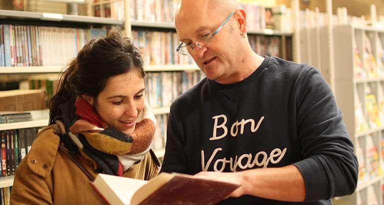 Photo de deux personnes lisant un livre
