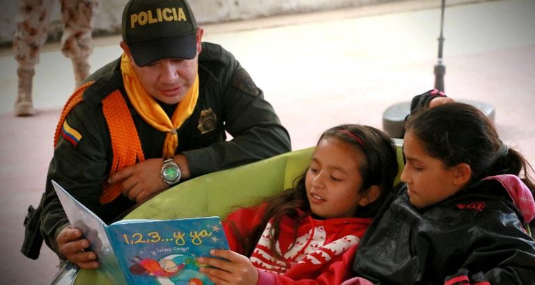 Photo d'un policier racontant une histoire à deux jeunes filles