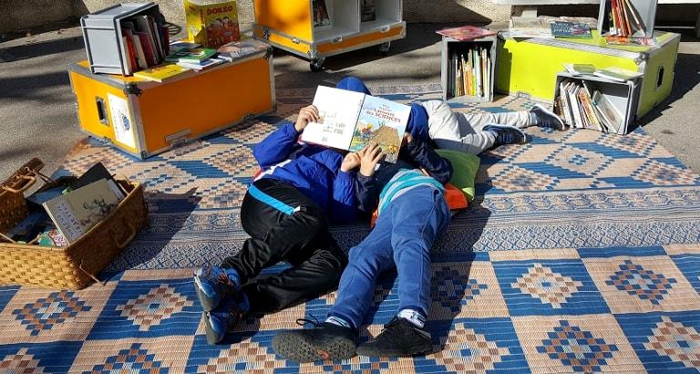 Photo d'enfants lisant par terre dans l'Ideas Box