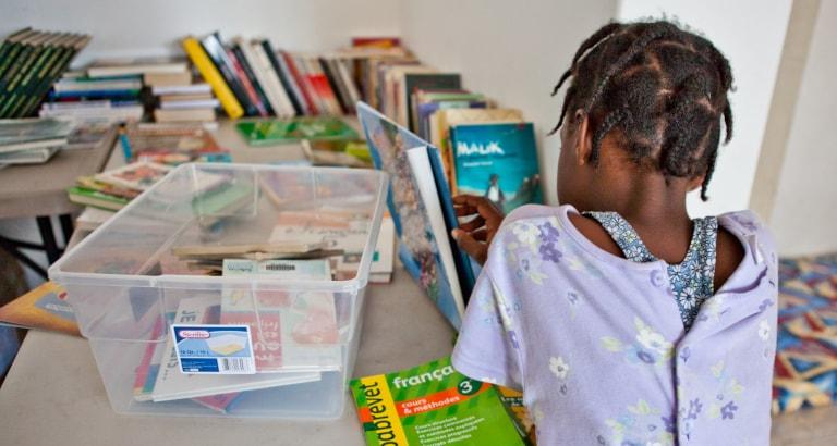 Photo d'une jeune fille de dos avec des livres